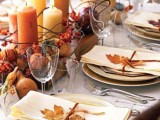 a neutral and organic wedding tablescape with earthy-colored candles, nuts, gourds and fall leaves that accent each place setting is very cozy and lovely