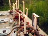 a fall woodland wedding tablescape with pink blooms, fall leaves, antlers and tall and thin candles, gold cutlery and neutral linens is awesome