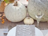 a neutral rustic fall wedding tablescape with a neutral runner, pumpkins, blooms, gourds and other stuff plus a cool printed menu is awesome