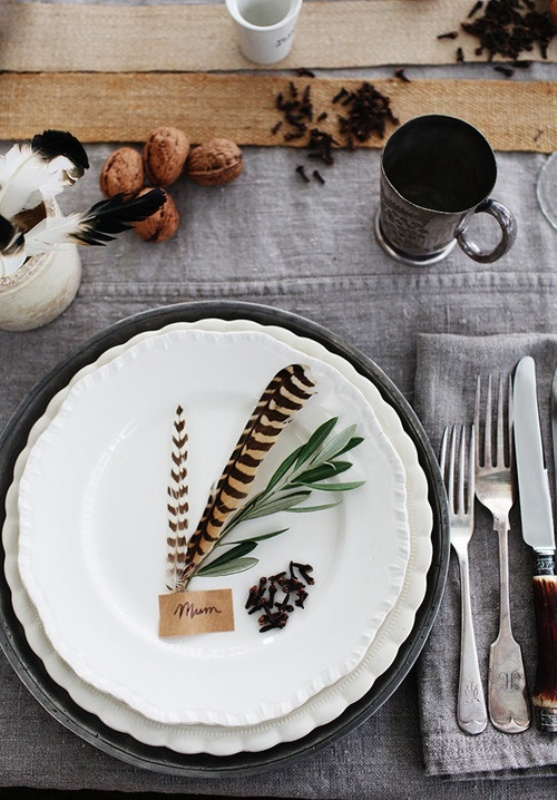 a beautiful organic fall wedding tablescape with grey linens, burlap, feathers, nuts and greenery plus metal mugs is cool and easy