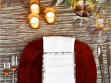 a pretty and bright fall wedding tablescape with a silver tablecloth, super bold floral arrangements, candles, a rich-stained wooden charger and elegant cutlery is all-cool