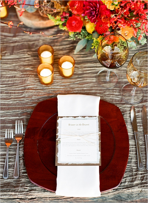 a pretty and bright fall wedding tablescape with a silver tablecloth, super bold floral arrangements, candles, a rich stained wooden charger and elegant cutlery is all cool