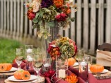 a bold wedding tablescape with a burgundy table runner, bold floral centerpieces, candles and pumpkins on each place setting is a bold and cool idea