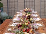 an amazing bold fall wedding tablescape with brigth fall blooms, greenery, berries, gourds, pumpkins, tie-dye napkins and gold cutlery is very cool