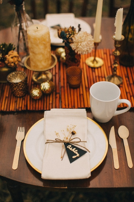 a glam fall wedding tablescape with a bamboo table runner, candles, dried flowers, Christmas ornaments, wooden cutlery for a sustainable touch