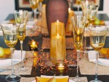 a rust and orange fall wedding tablescape with amber chargers, amber glasses, candles, some faux branches with sparkles and a large vase with them