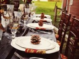 a rustic fall wedding tablescape with an uncovered table, elegant white plates and bright napkins, pinecones, tall wooden candleholders and pillar candles is awesome