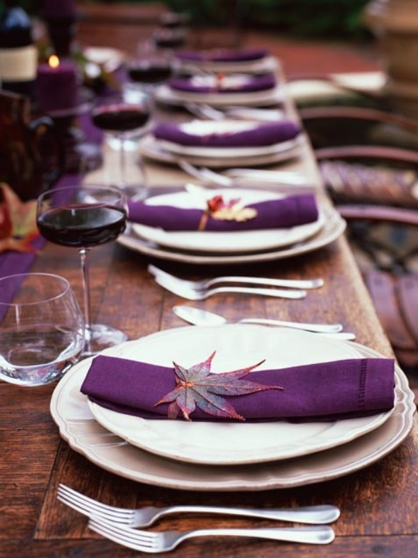 a bright fall wedding table setting with an uncovered table, purple napkins, a purple table runner and bright fall leaves is amazing