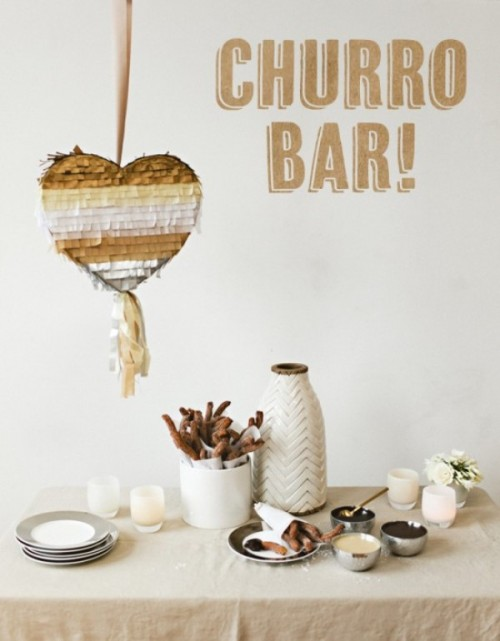a fun and bold churro bar done with a heart-shaped pinata, blooms and candles