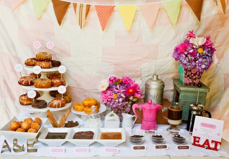 a colorful rustic donut bar with a bright bunting, bright blooms, donuts and various dips and toppings