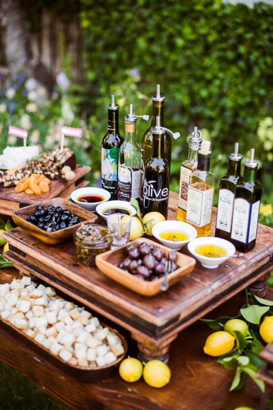 an olive oil tasting bar with various kinds of olives, olive oil, nuts, some bread and cheese is perfect for a Tuscany wedding