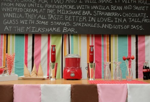 a colorful retro ice cream bar with a bright striped backdrop, strawberries, cones and an oversized chalkboard sign