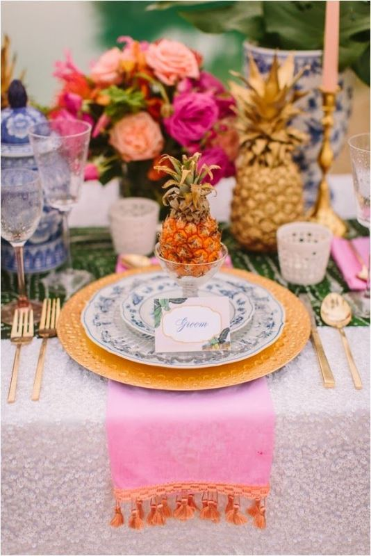 a bright and colorful wedding tablescape with a green printed runner with lots of fruit and candles, gold chargers and cutlery and a colorful floral centerpiece