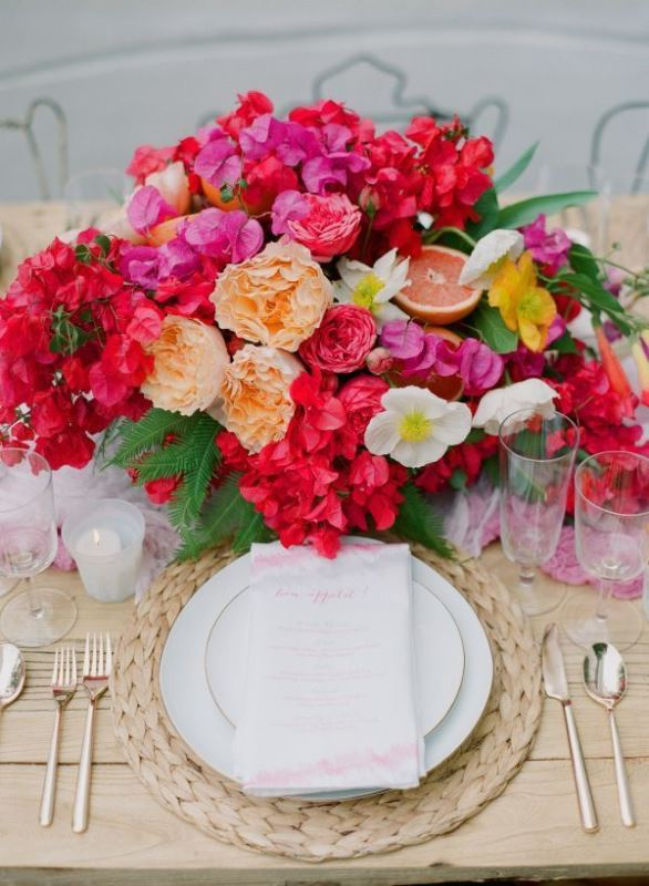 a bold tropical wedding tablescape in neutrals, with a woven charger and a bold floral centerpiece with citrus and fruits