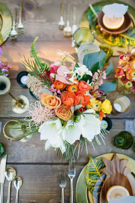 a colorful tropical wedding tablescape with a super bold floral centerpiece and tropical leaves, candles and colored glasses