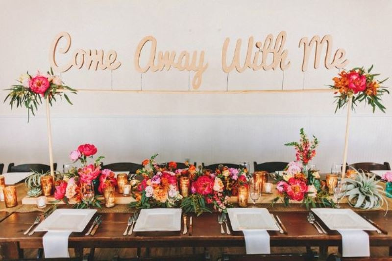 a bright tropical wedding tablescape with pink and red blooms and greenery, candles, succulents, air plants and some floral arrangements over the table