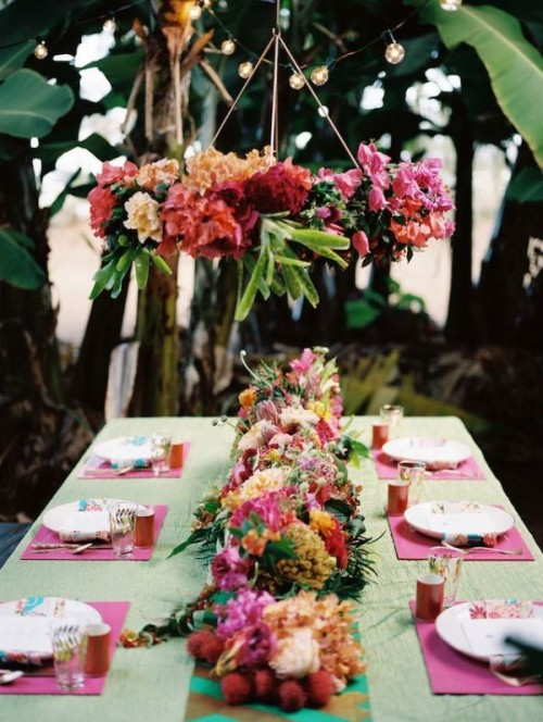 a colorful tropical wedding tablescape with a green tablecloth and pink placemats, a bright floral and fruit table runner and a bold installation overhead