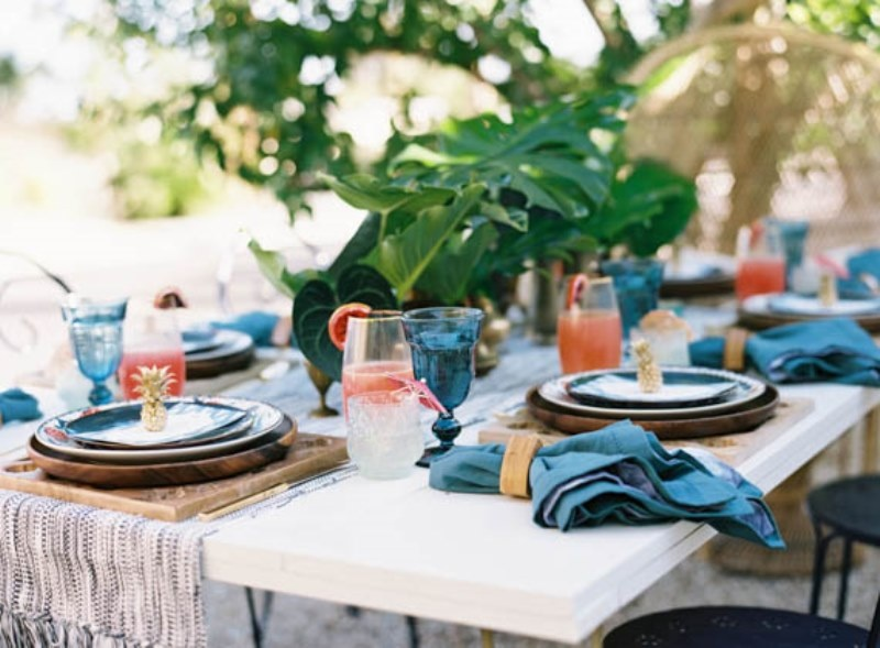 a simple yet bright wedding tablescape with a neutral table runner, blue napkins, blue glasses and bold cocktails