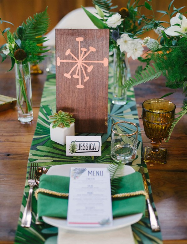 a bold tropical wedding tablescape with a bold tropical table runner, green napkins and tropical leaves for decor, colorful glasses
