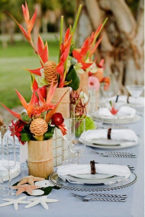 a bright tropical wedding tablescape with bold florals, starfish, tropical leaves and neutral linens and a striped tablecloth
