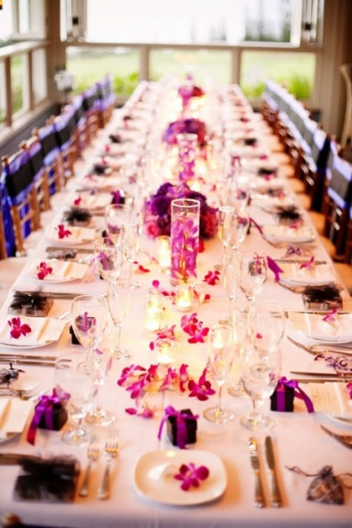 a bold white and purple wedding tablescape with bold purple blooms and napkins, candles and white linens is very elegant and refined