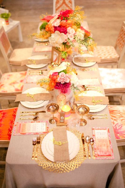 an elegant and colorful wedding tablescape with bold florals and gold chargers, gold cutlery and goblets looks very refined