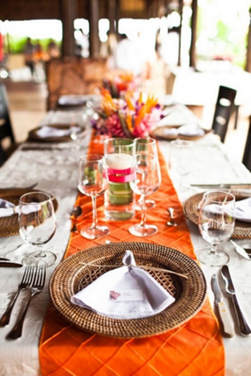a bold wedding tablescape in neutrals and orange, with woven chargers, bright blooms and simple cutlery