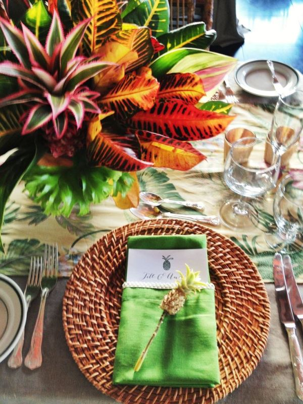 a bold wedding tablescape with a tropical tablecloth and napkins, bold leaves, woven chargers and cutlery