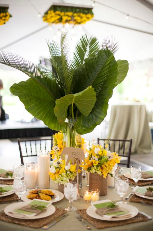 a bold tropical wedding tablescape with mustard blooms and oversized tropical leaves, woven chargers, candles, green napkins