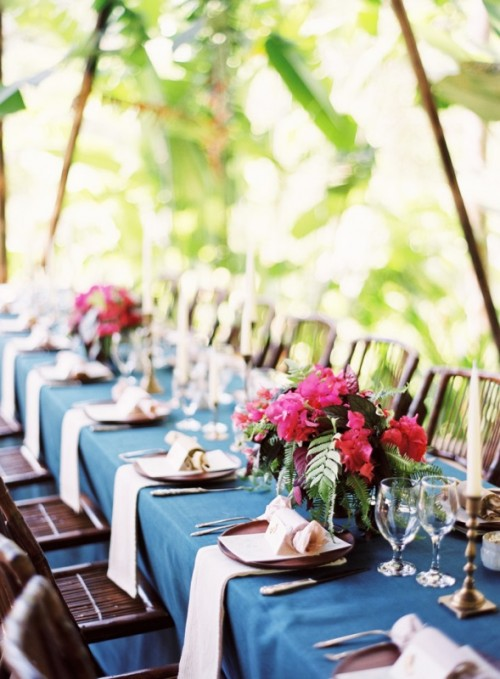 a bright tropical wedding tablescape with a navy tablecloth, blush napkins, super bold floral arrangements and candles