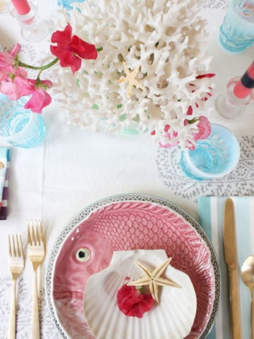 a creative tropical beach wedding tablescape with pink and blue touches, corals, starfish, a pink fish plate and blooms and blue goblets