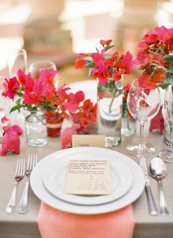 a tropical wedding tablescape with neutral linens, bold red and pink florals and neutral cards and cutlery