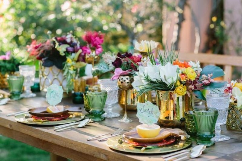 a colorful wedding tablescape with gold chargers, cutlery and vases, green glasses and bright blooms