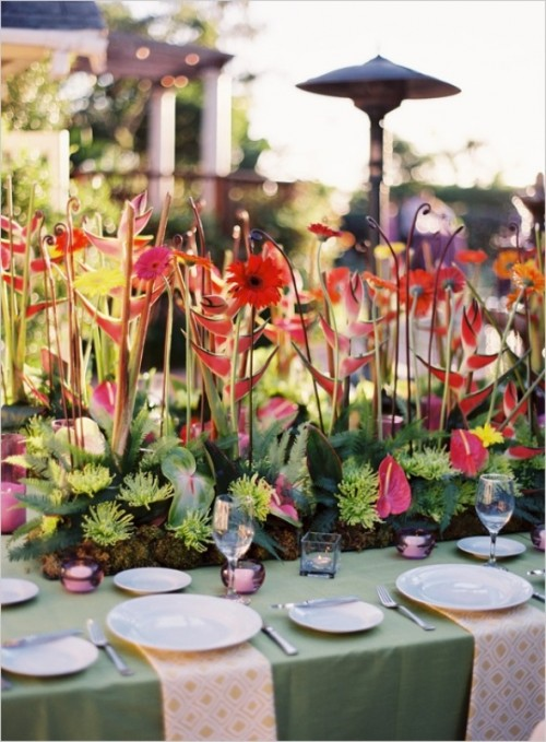 a whimsical tropical wedding tablescape with a green tablcloth and printed napkins and a unique floral, greenery and succulent centerpiece which seems to be growing from the table