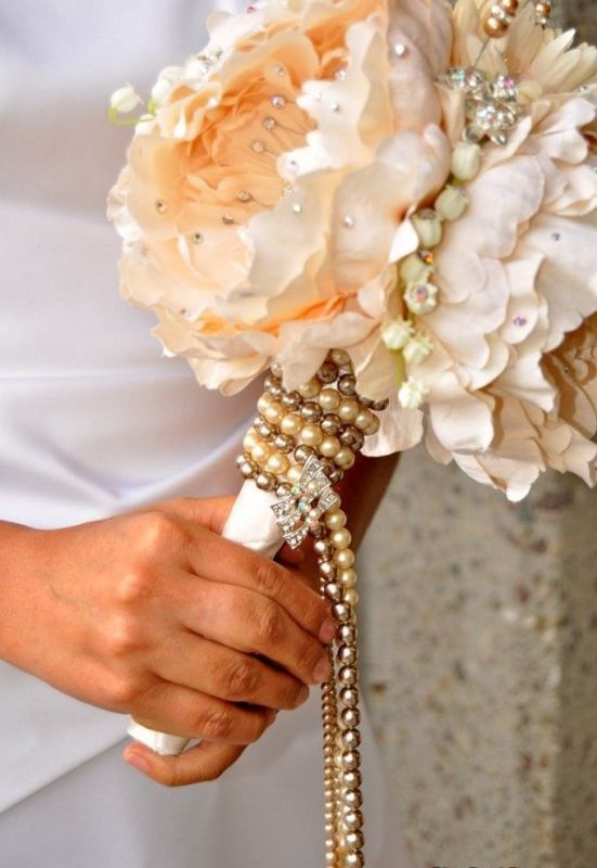 a pearl necklace wrap with a brooch   take a vintage necklace of your relative to add a personal touch to the bouquet