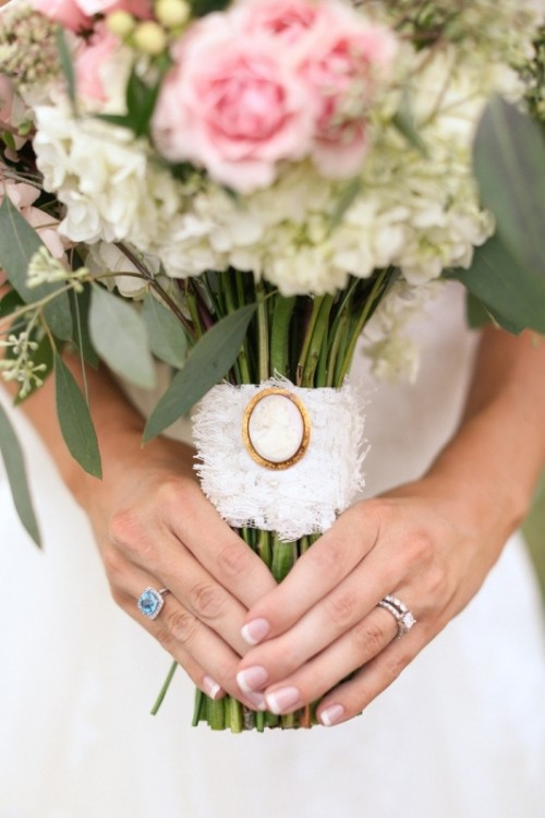 a white lace bouquet wrap with a large opal brooch is a chic idea for a refined look