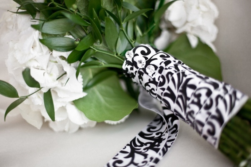 a black and white ribbon wrap with rhinestone pins is a very chic and refined idea