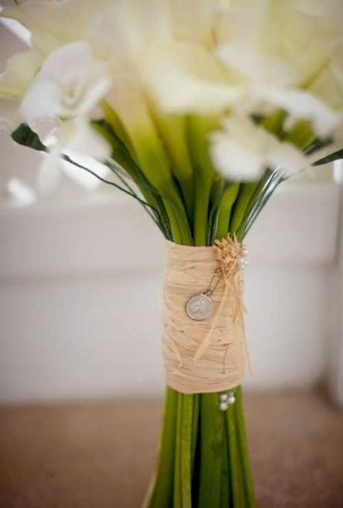 a raffia bouquet wrap with pearls and a mini coin is a cool idea for a rustic wedding bouquet