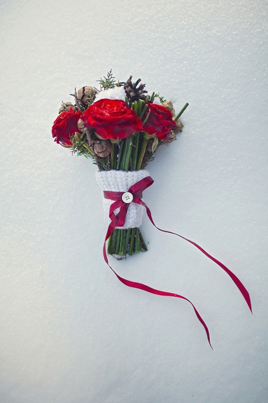 a white knit wrap with a red bow and a button on top is a great and cozy idea to accent your winter wedding bouquet