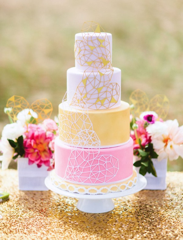 a bright and fun yellow and white wedding cake decorated with geometric hearts is a lovely and bold idea for a modern wedding