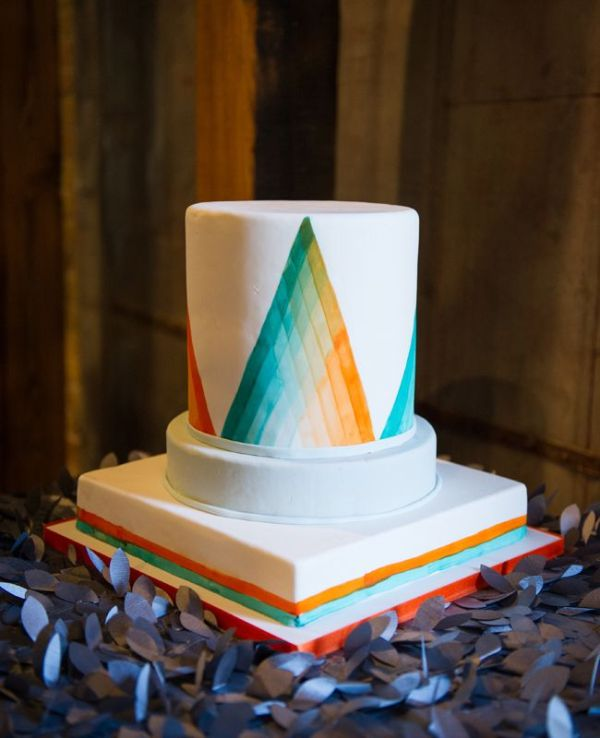 a round wedding cake with colorful ombre triangles painted on the surface looks outstanding and extra bold