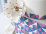 a round and square wedding cake with colorful triangles and a large white sugar bloom on the side is a lovely and bold idea for a modern and colorful wedding