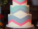 a round wedding cake decorated with squa, pink and blue lines forming chevrons looks bold and very unusual and will fit a modern wedding