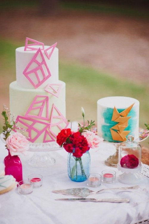 a gorgeous wedding cake with hot pink sugar shards that cover it and a white wedding cake with turquoise brushstrokes and gold triangles covering it is a lovely idea