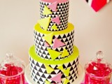a round wedding cake with black and white triangles covering the tiers and bold pink and neon yellow tops and triangles all over the cake