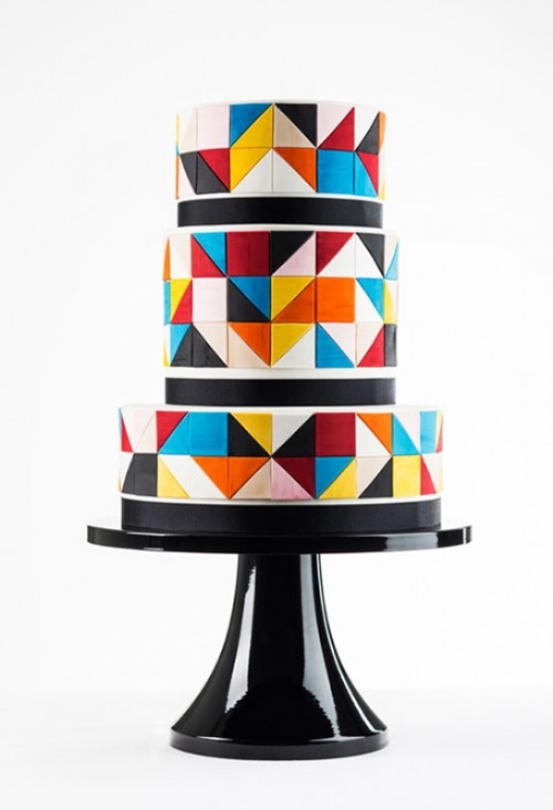 a round wedding cake with super colorful triangles covering it and black lines to highlight each tier is a lovely idea for a bold wedding