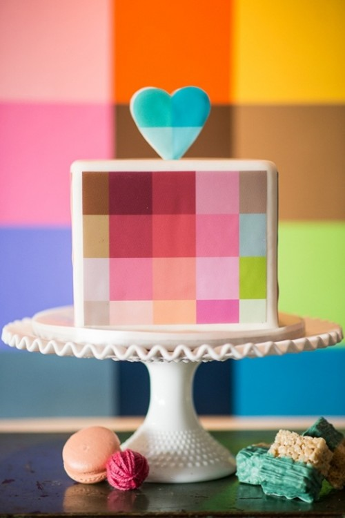 a square wedding cake with colorful squares painted on it and a pretty color block heart topper is a fresh idea for a modern wedding