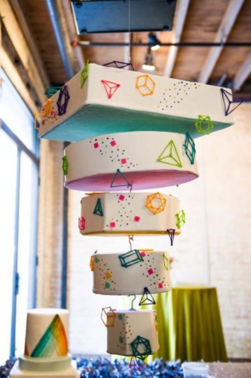 a unique suspended wedding cake with mismatching tiers covered with 3D triangles and squares, with colorful confetti and dots is a lovely idea for a modern wedding wedding and it makes a great impression
