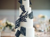 a white round wedding cake decorated with 3D black triangles and rhombs is a very stylish and cool idea