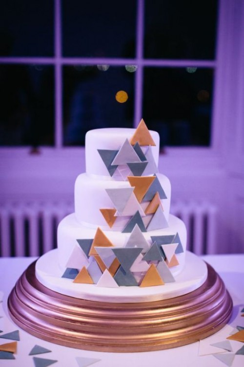 a round white wedding cake with colorful 3D triangles covering each tier is a stylish and cool idea for a modern wedding